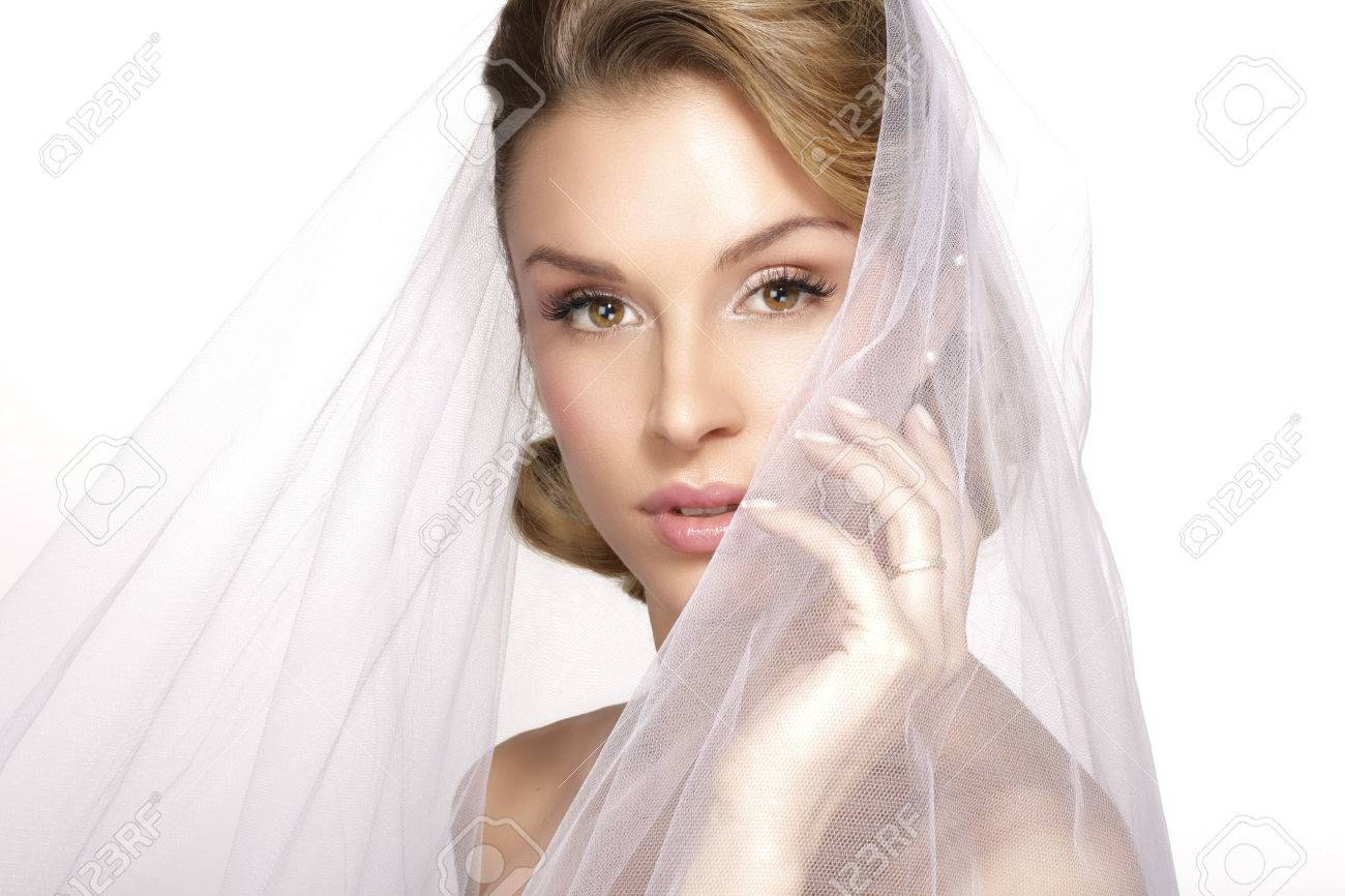 portrait of young woman in wedding dress posing with bridal veil on white - 36913102