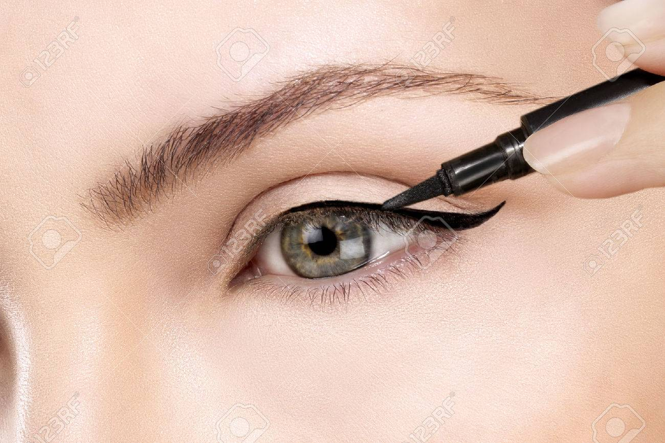 model making eyeliner on eye closeup - 38789029