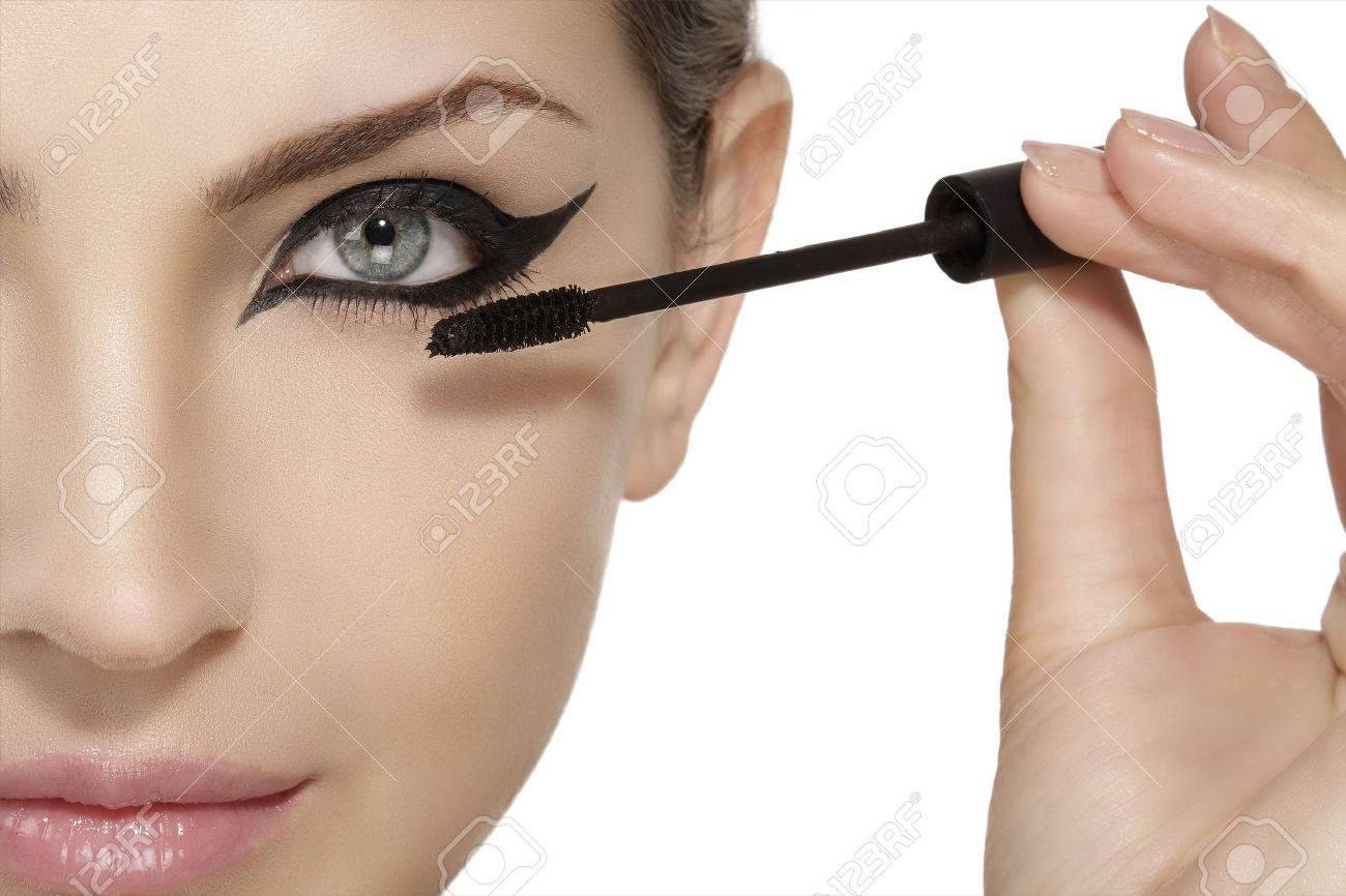 Beautiful model applying mascara on eyelashes close up on white - 37805738