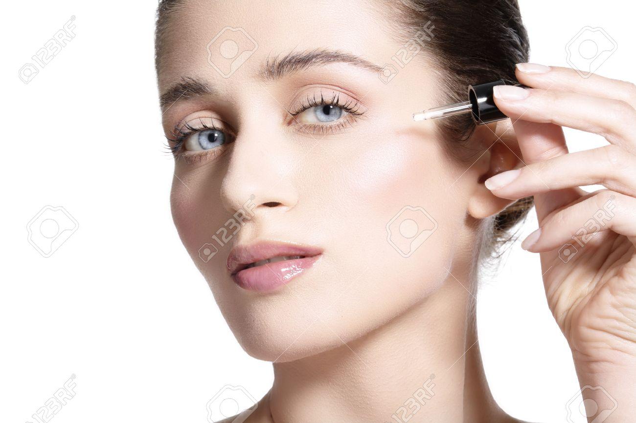 beautiful model applying a skin serum treatment on white - 40899263