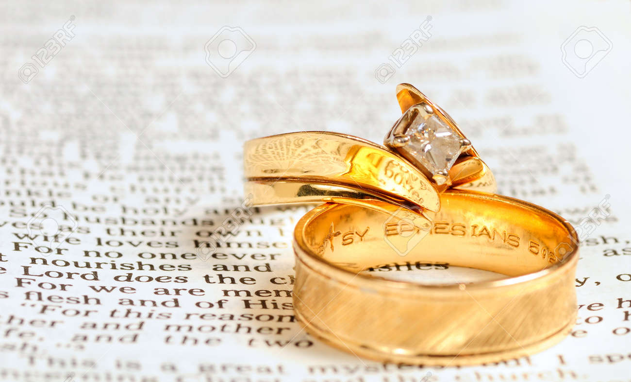 Two Gold Wedding Rings Rest On The Marriage Passage From Ephesians