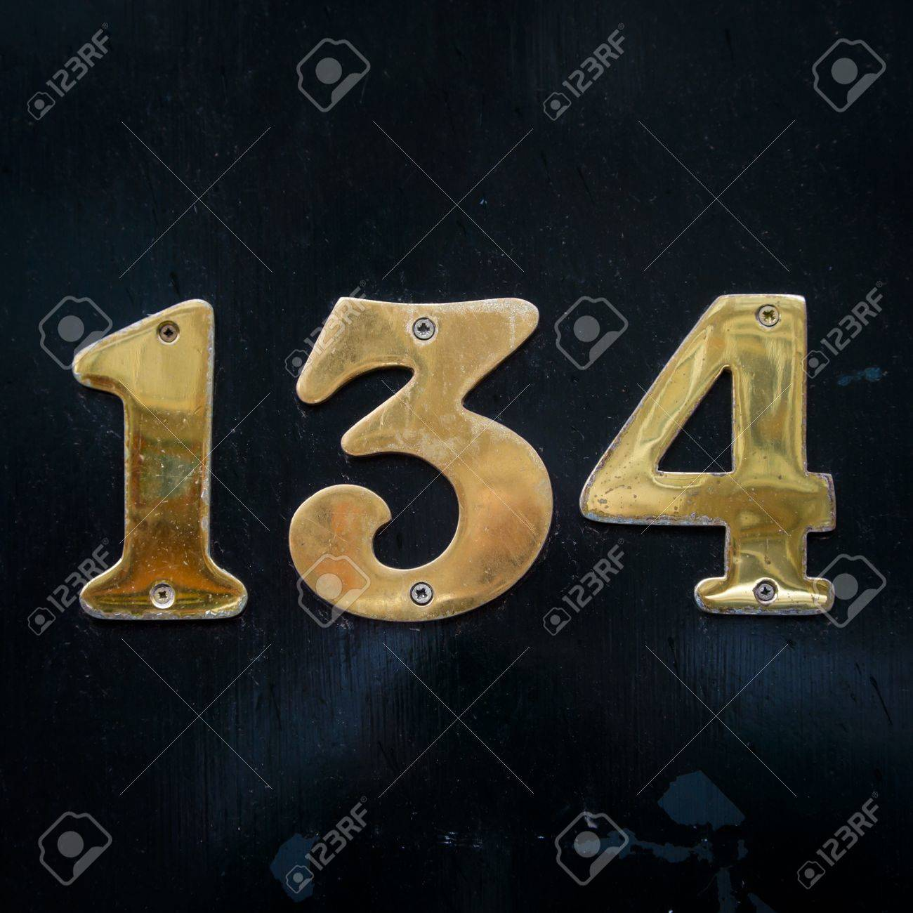 shiny, gold colored house number 134 on dak background Stock Photo -  13255063