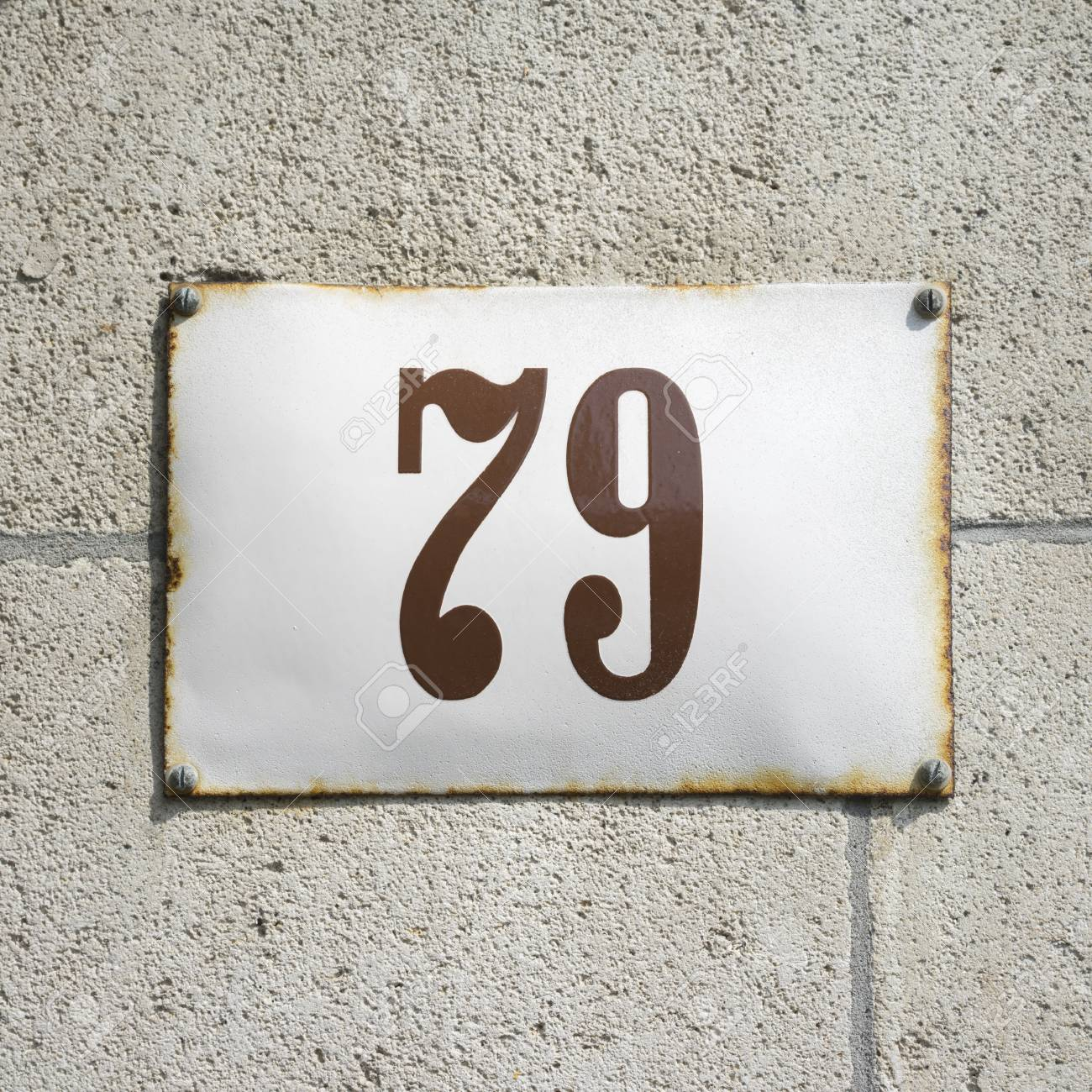 enameled house number on a wall of natural stone stock photo