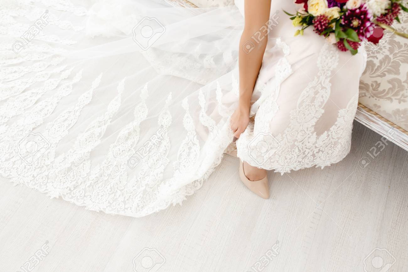 The Bride Is Wearing Wedding Shoes In A Wedding Dress