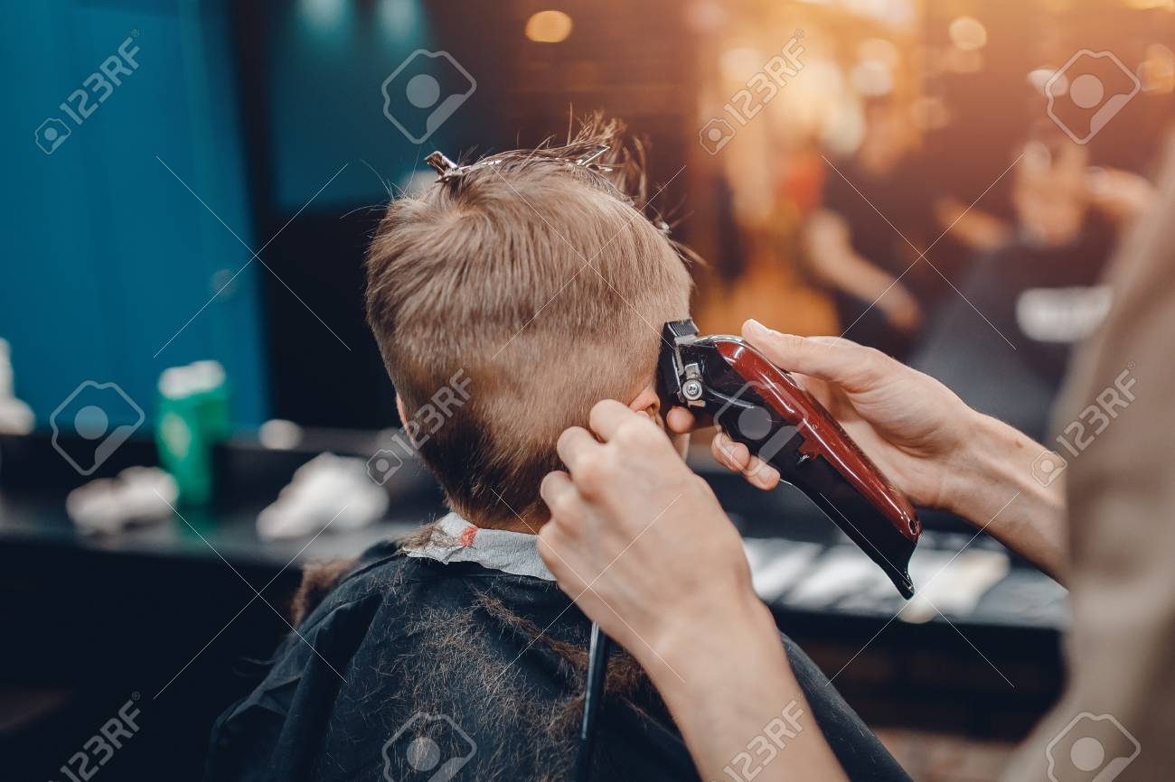 Barber shop. Barbershop Hairdresser makes hairstyle a man with a beard child - 88686530