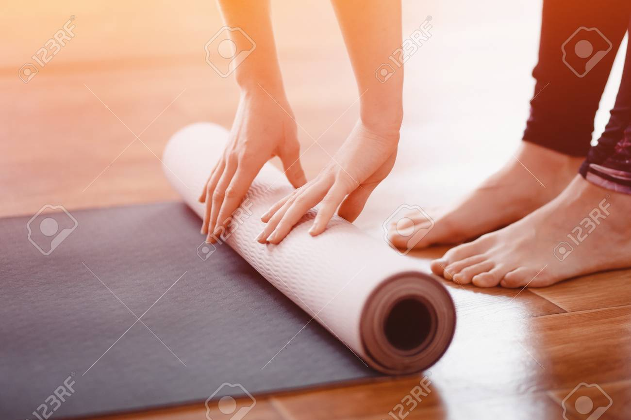 Yoga. Close-up woman folding roll fitness or yoga mat after working out home in living room. Concept healthy life. - 90061501