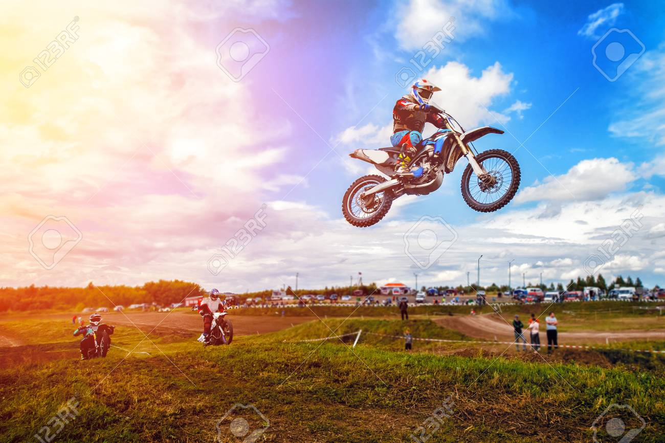 Racer on motorcycle participates in motocross cross-country in flight, jumps and takes off on springboard against sky. Concept active extreme rest. - 95190220