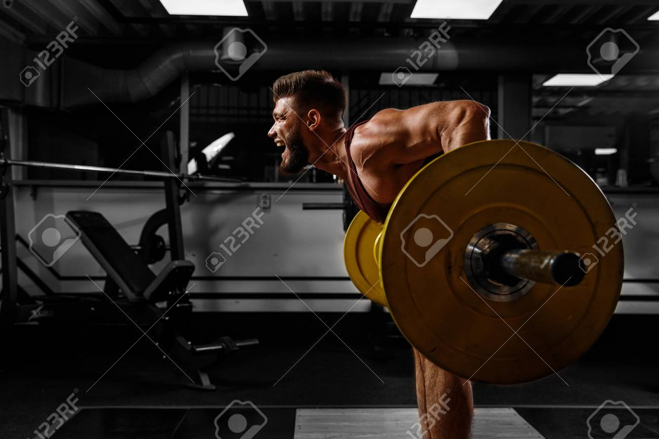 Sports background. Young athlete lifts barbell to his chest. Concept workout - 109711331