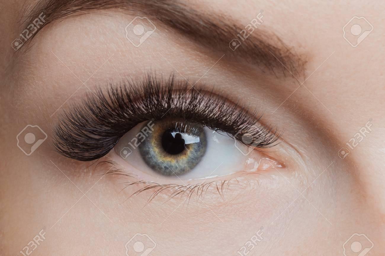 Eyelash extension procedure. Beautiful female eyes with long lashes, closeup - 107413731