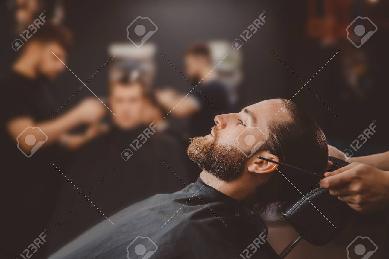 Barber shop. Man in barbershop chair, hairdresser styling his hair - 108264117