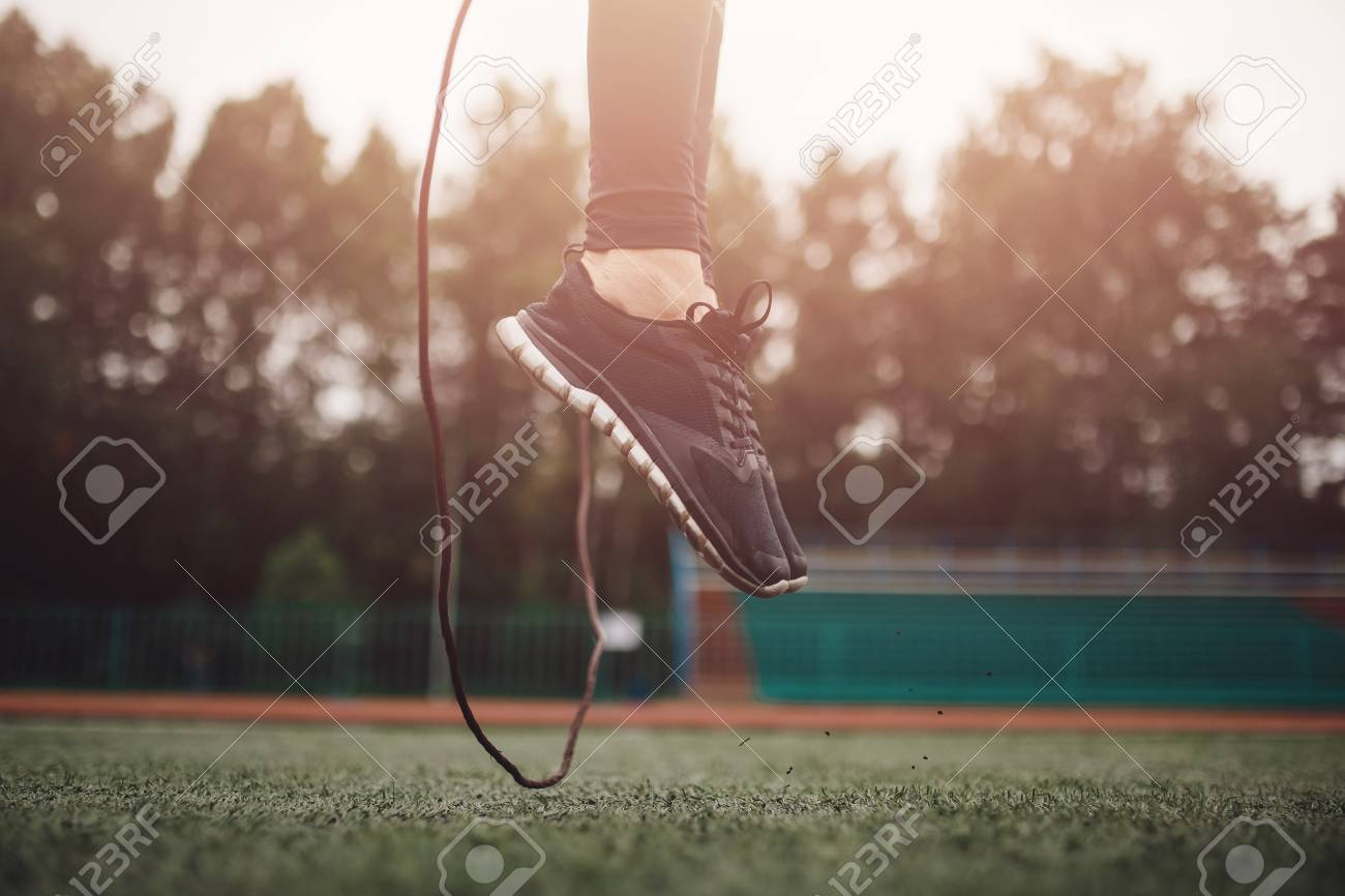 Male athlete performs exercise jump on rope in stadium sport workout. - 108120116