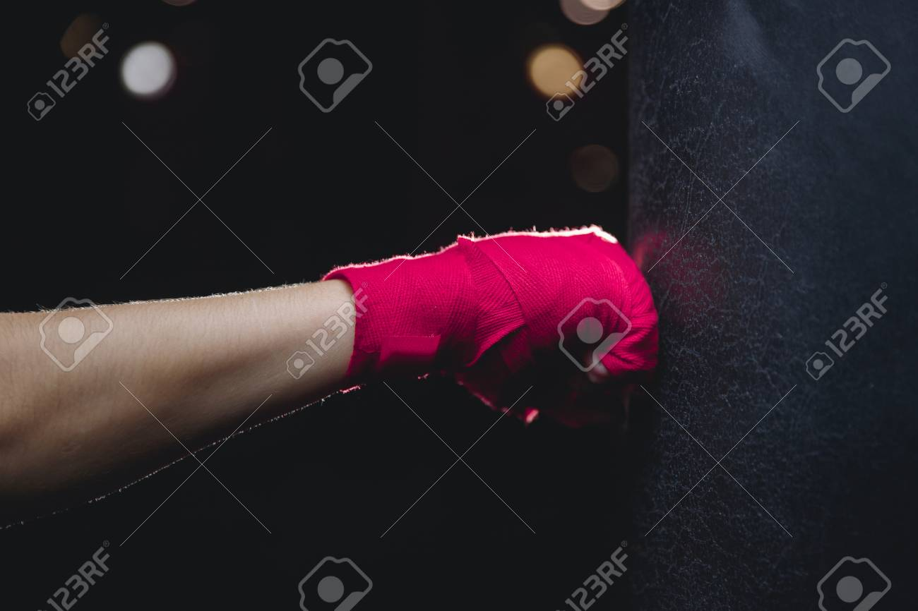 Close-up of hand in fist pink protective insulating bandage hits punching bag on black background. Concept Boxing - 112554932