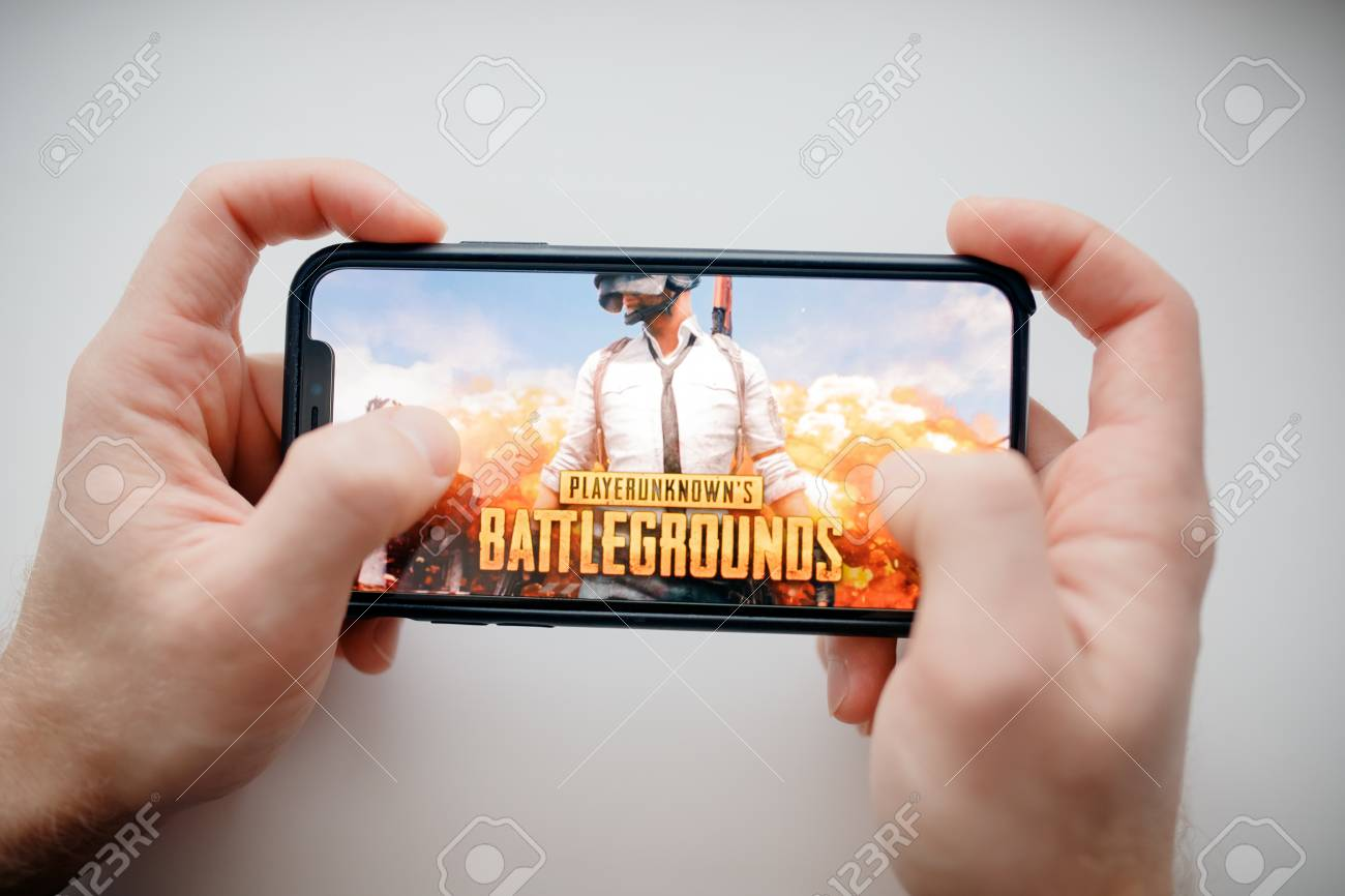 Moscow, Russia - January 1, 2019 : Man holding smartphone with Player Unknown Battleground PUBG online shooting gaming. - 115125633