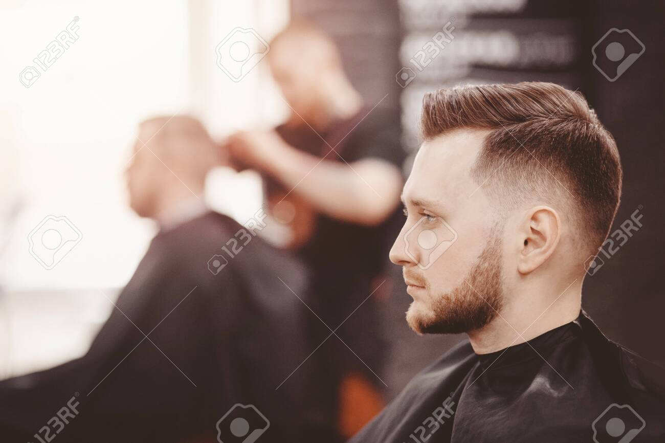 Barbershop banner. Man in barber chair, hairdresser styling his hair - 122132364