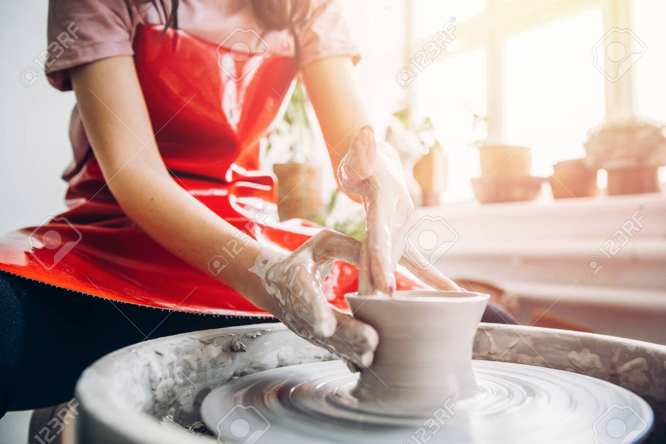 Young woman in red apron works behind potter wheel with length, making handmade plate. Concept of concentration, creativity hand made. - 122773678