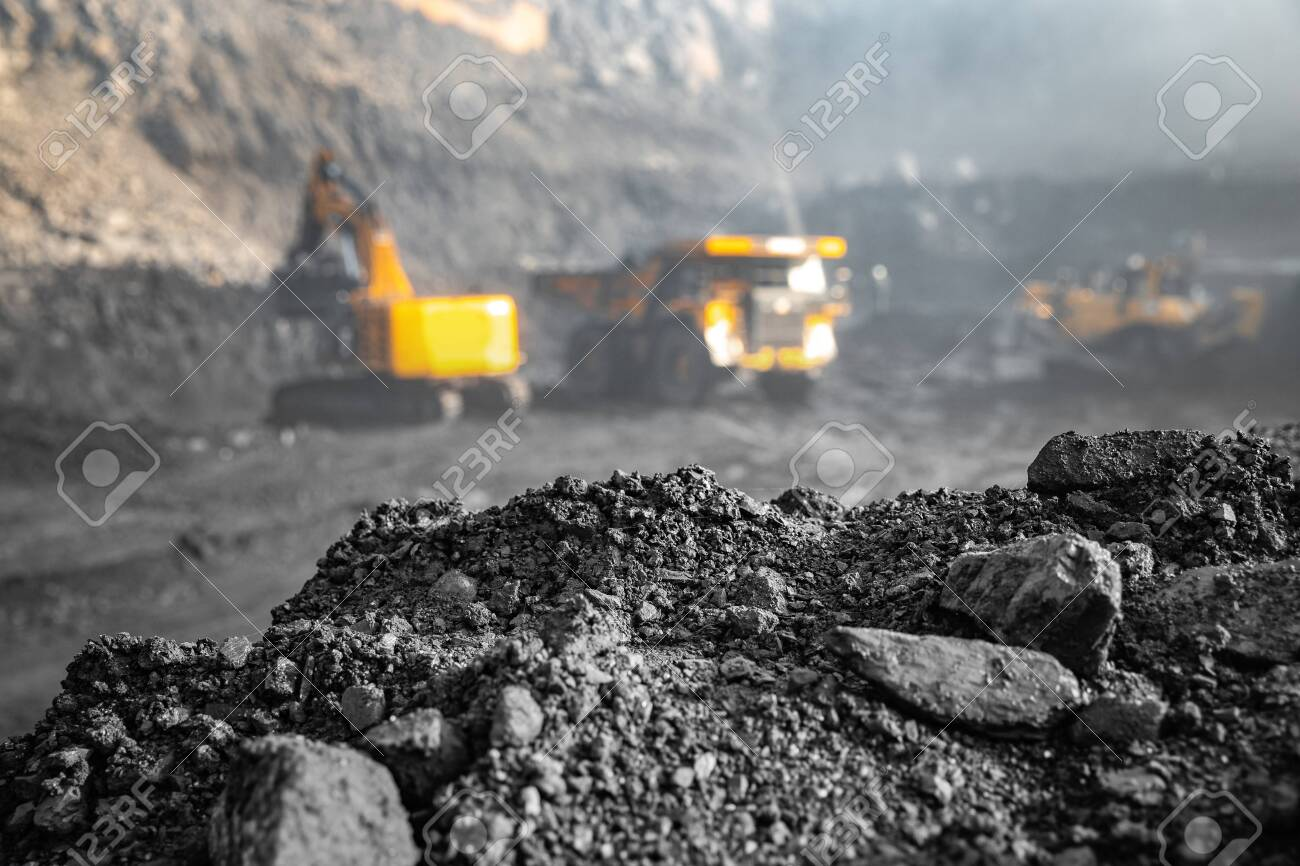 Coal open pit mine. In background blurred loading anthracite minerals excavator into large yellow truck. - 132172911