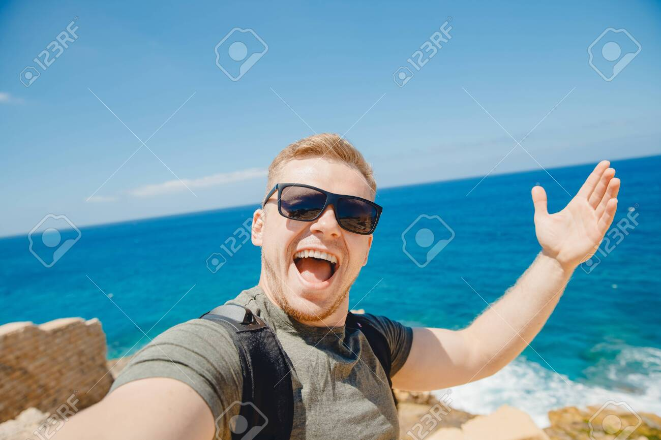 Happy traveler man taking selfie photo in sunglasses on background of bruise sea with backpack. Travel concept - 140261739