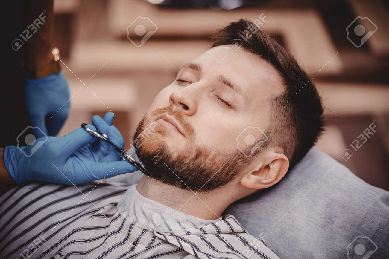 Close-up of barber with medical gloves shearing beard to man in barbershop. Haircut pandemic protection - 166261924