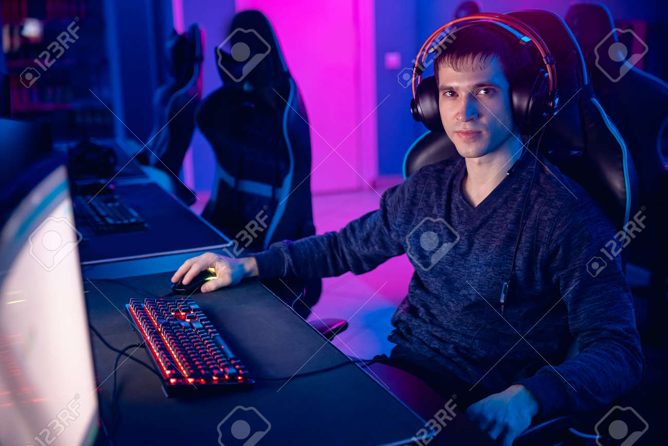 Portrait young man professional gamer playing online games computer with headphones, neon color - 170719161