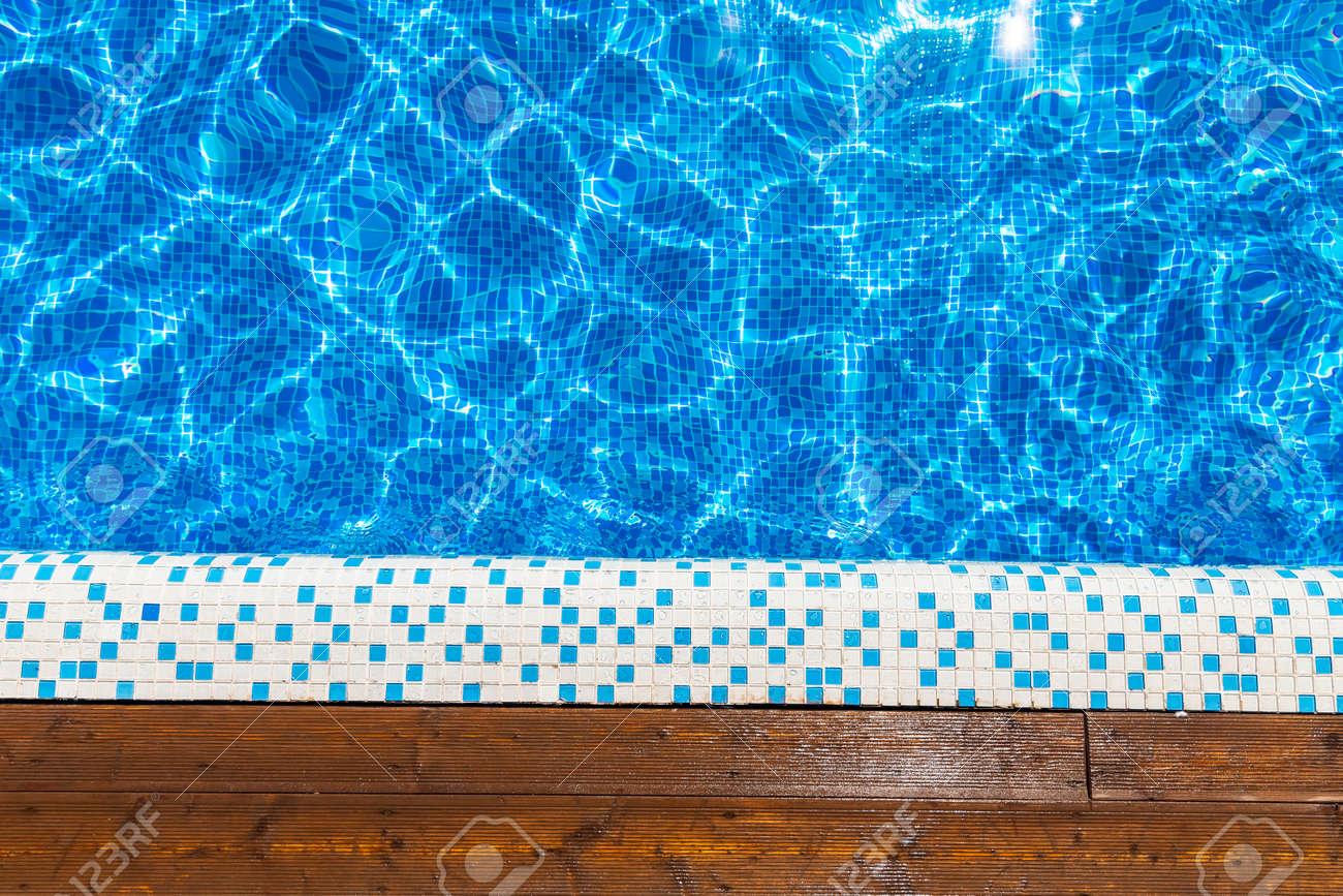 Top view blue swimming pool with teak wood flooring stripes sunlight - 166139696