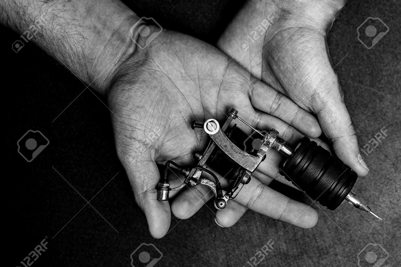 Man artist holding tattoo machine on hand, top view black and white color - 172921471
