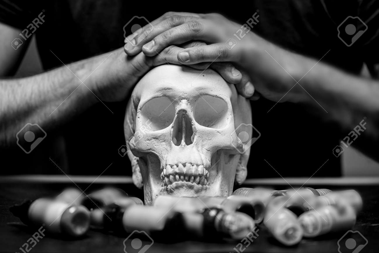 Tattoo artist folded hands on plaster skull surrounded by typewriter ink, black and white photo - 172921489