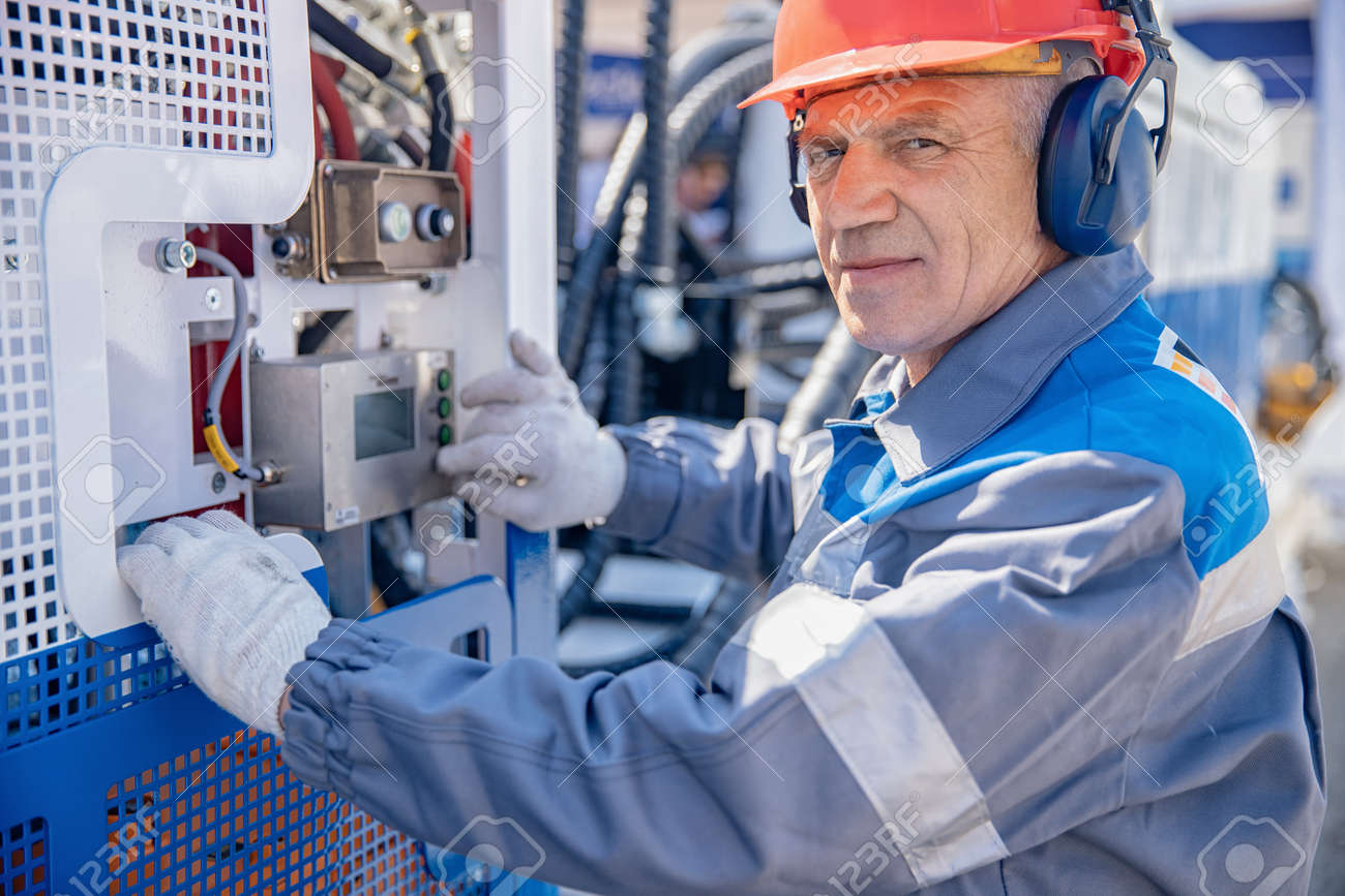 Industrial portrait electrician worker man at factory in hard hat and headphones performs start of equipment machine - 172921603