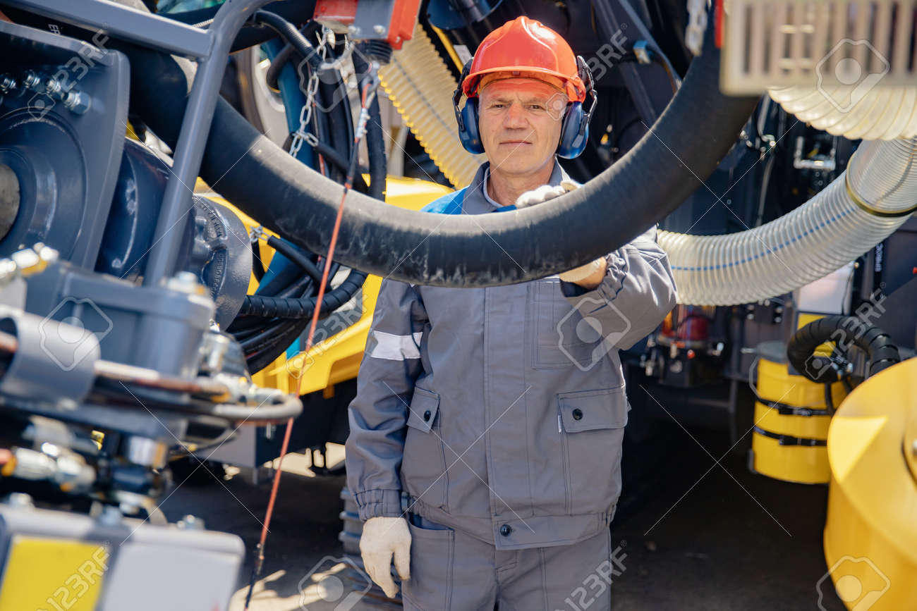 Industrial worker fuel electrician factory in hard hat and headphones monitors electric cable at oil well - 172921605