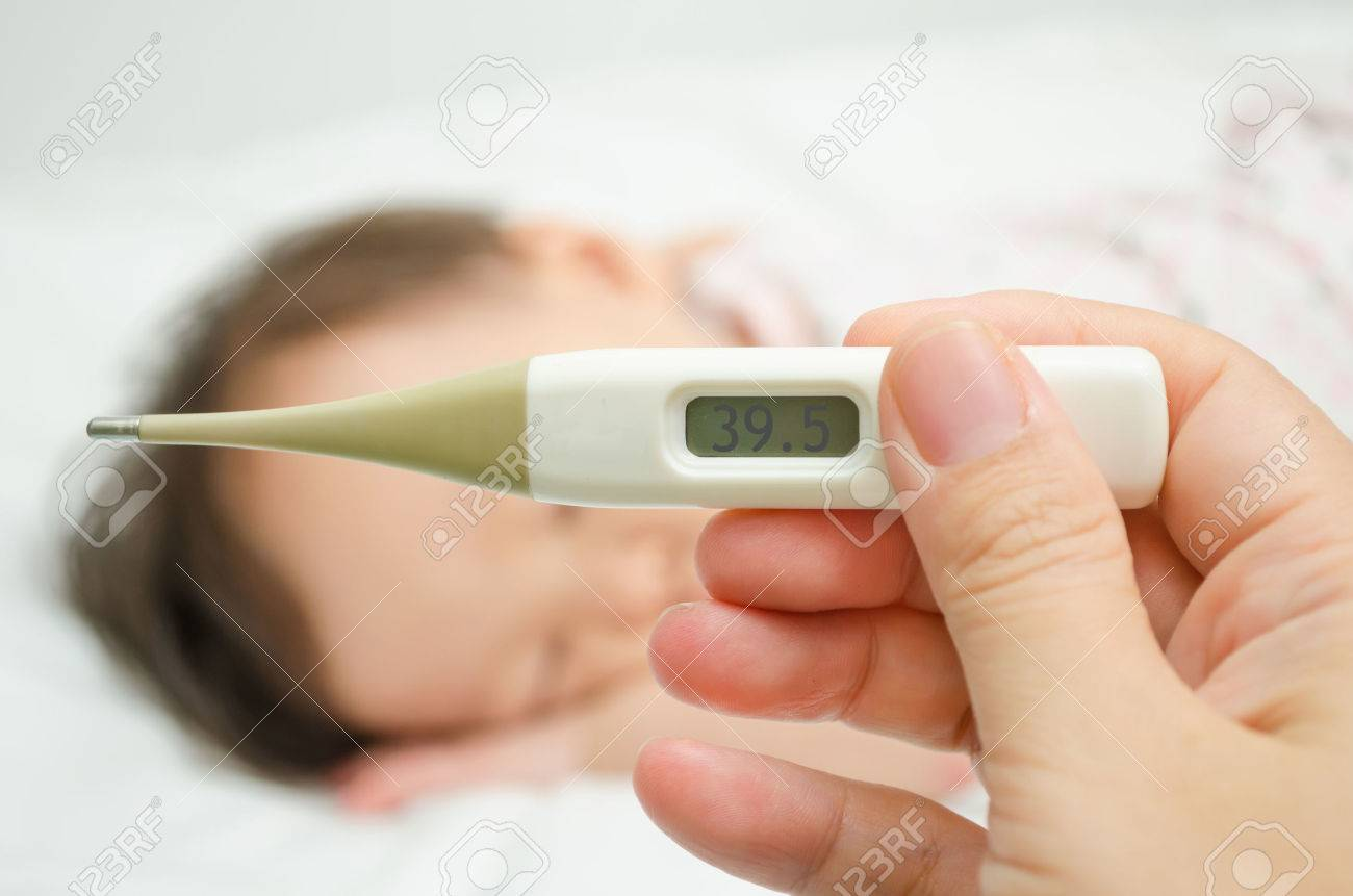 Mother holding thermometer foreground and sick little girl in bed Stock Photo - 30136487