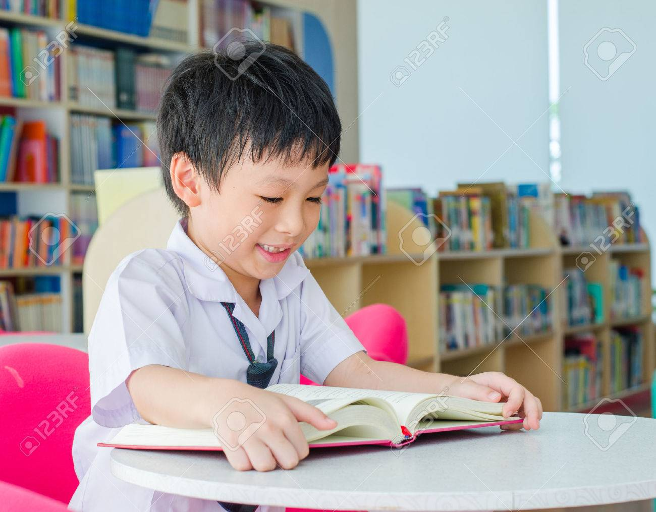 Asian schoolboy reading book in school library Stock Photo - 35107327
