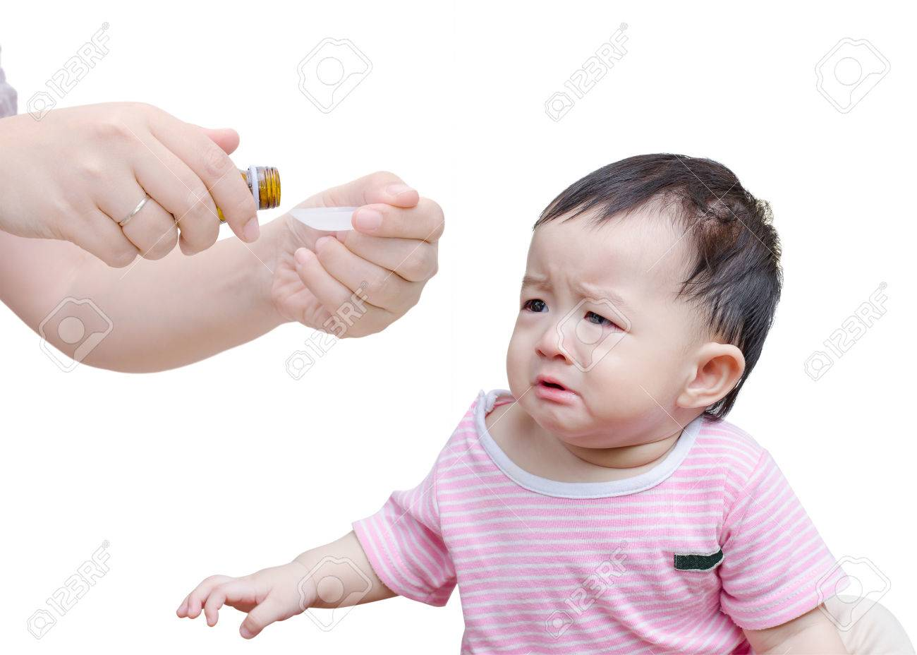 Woman's hands pouring medicine in a spoon foreground and crying baby over white background Stock Photo - 43163449