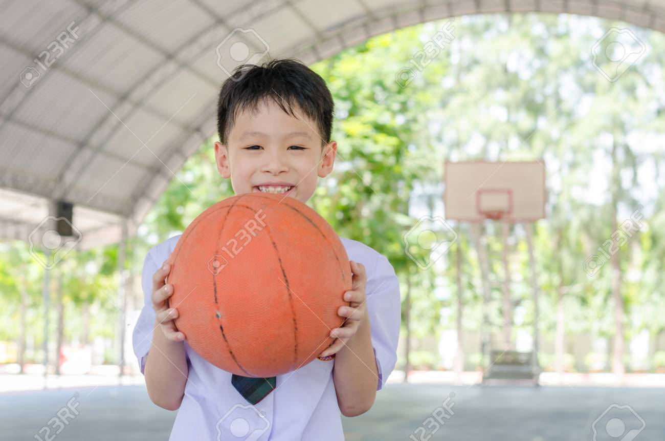 Little Asian student holding basketball at school Stock Photo - 48010312