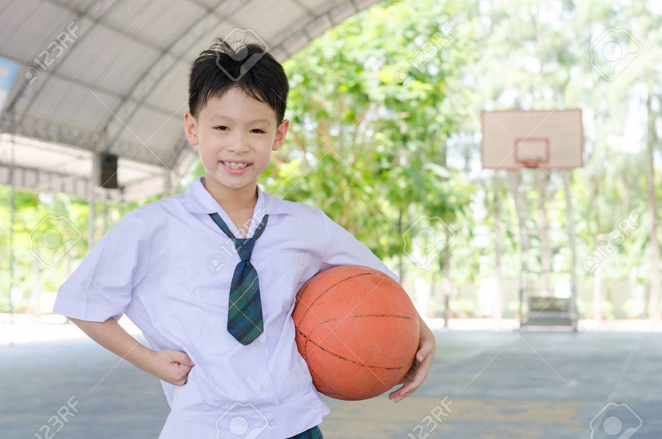 Little Asian student holding basketball at school Stock Photo - 48085544
