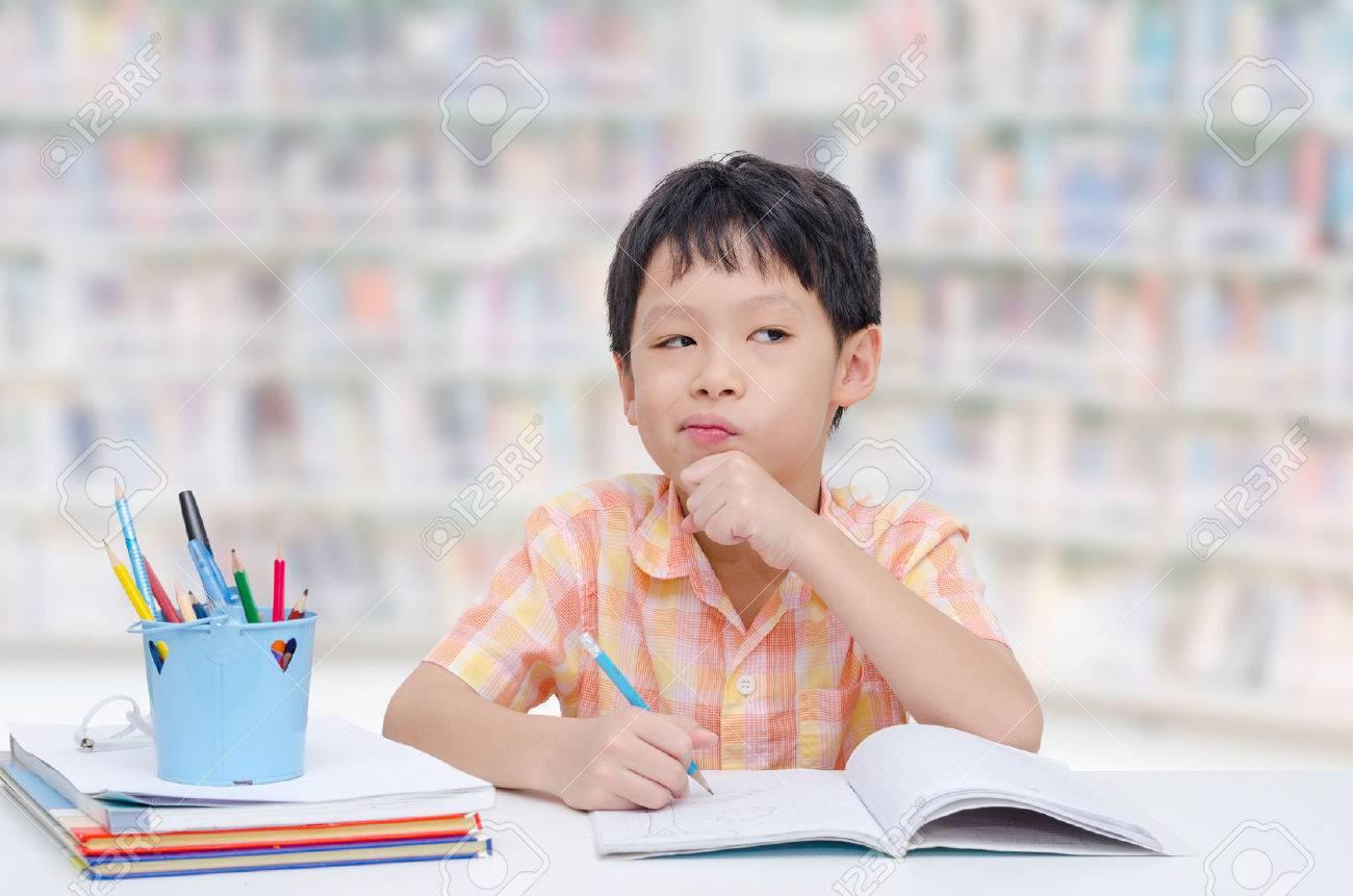 Little Asian boy thinking between doing homework - 51289340