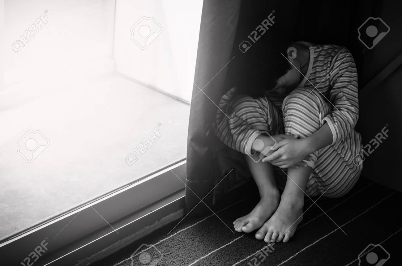 Stock photo young sad boy sitting on the floor