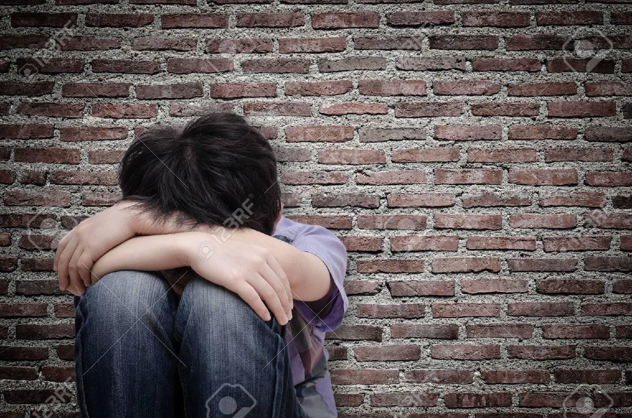 Little sad boy sitting on floor over old wall - 53135418