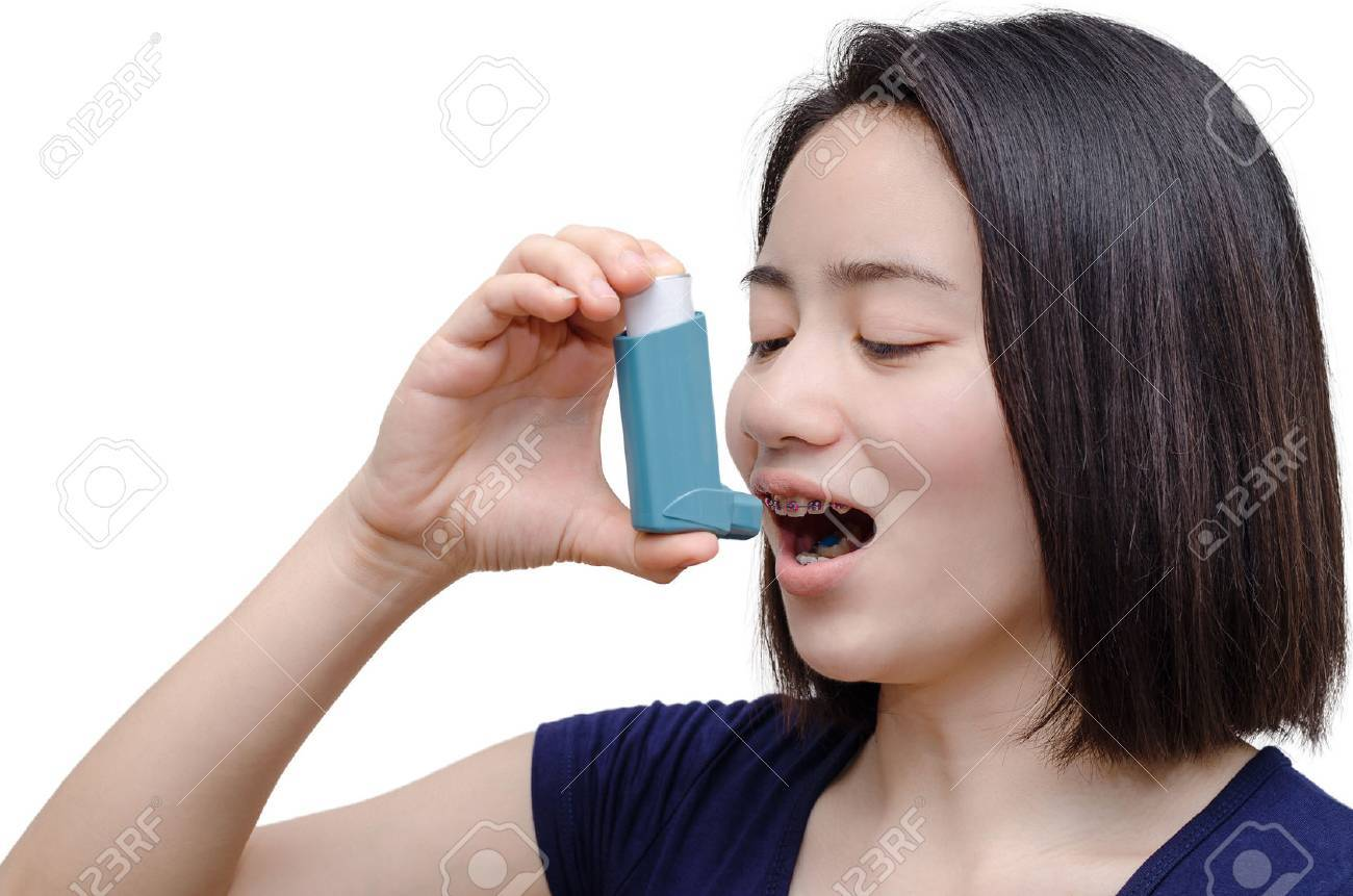 Young asian woman using inhaler over white background - 61321332