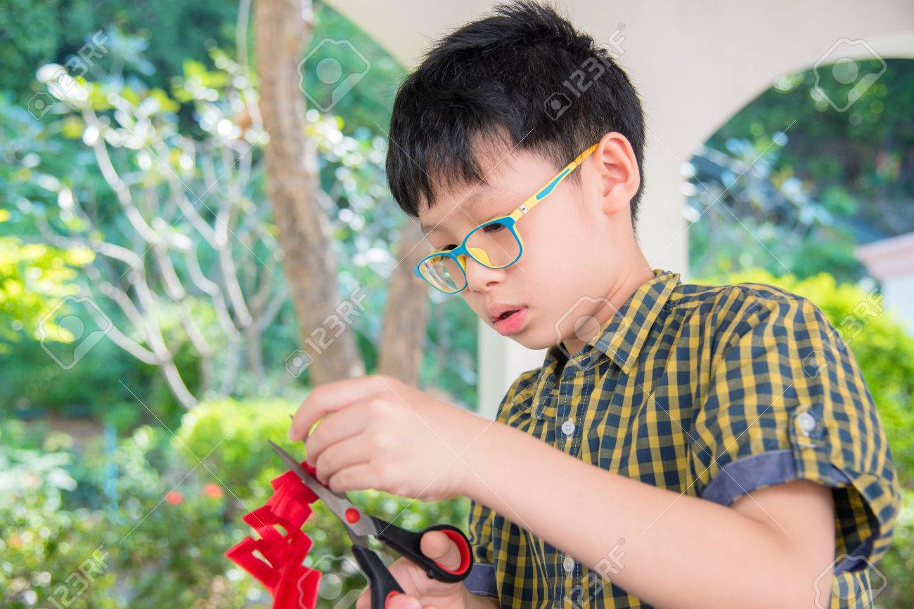 boy cutting paper Stock Photo - 75425364