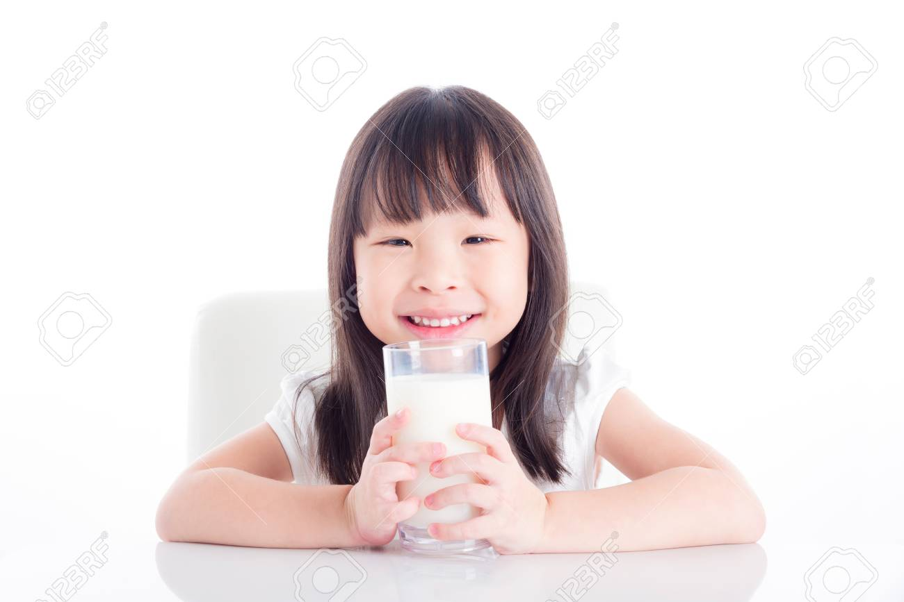 Little asian girl sitting and holding a glass of milk over white background - 87705093