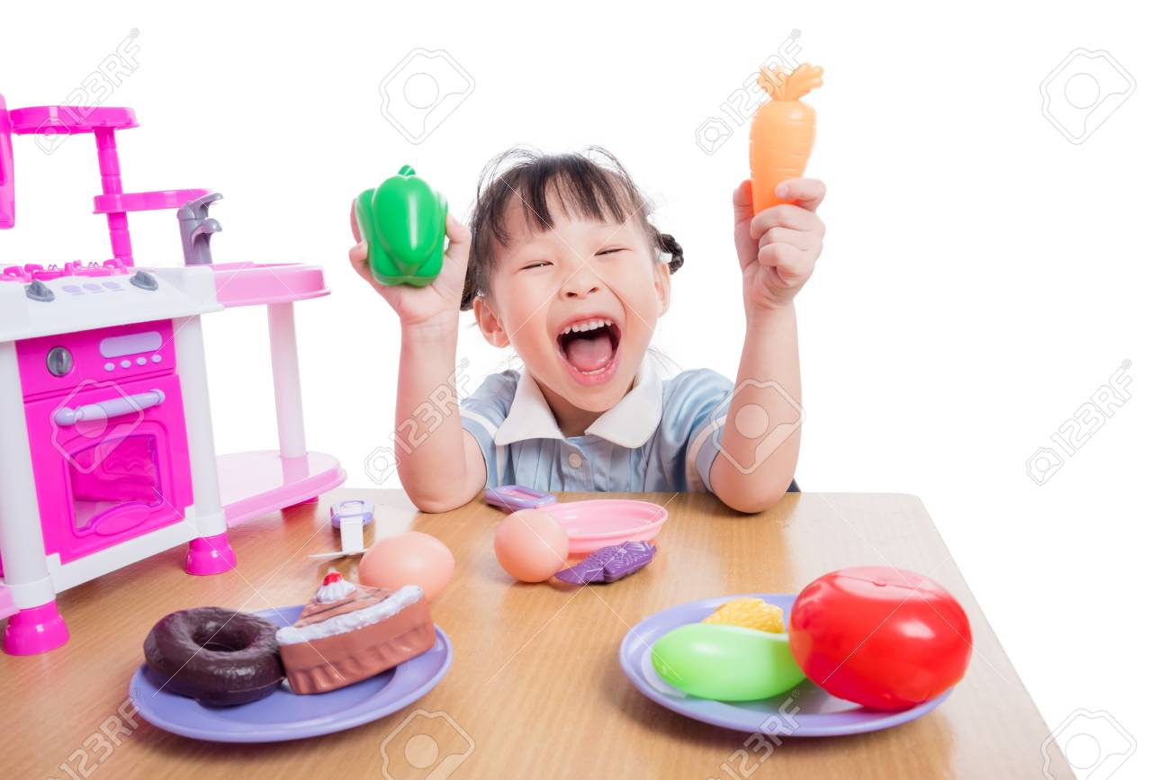 Girl playing kitchen toy on table - 95053279