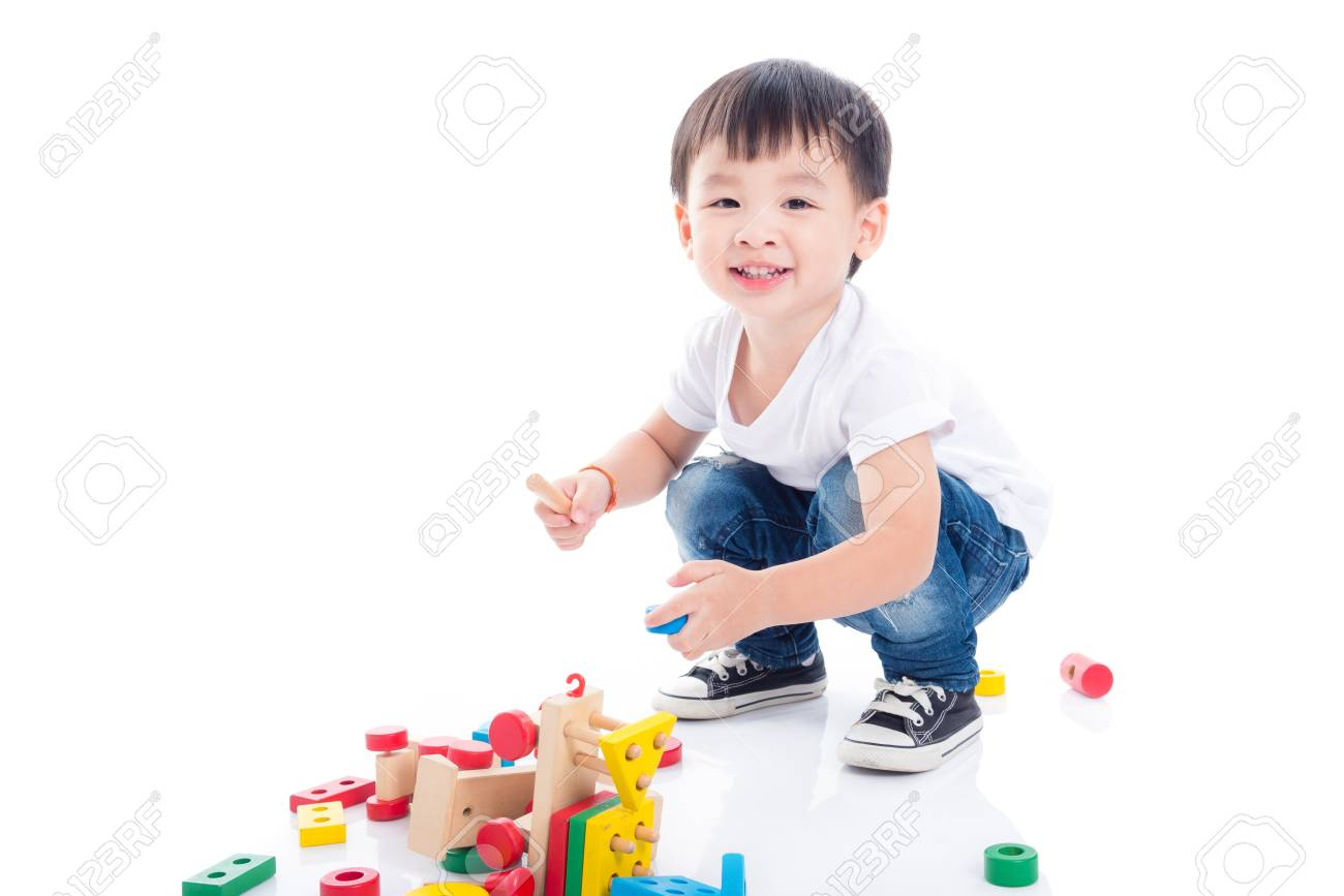 Little asian boy playing toy on the floor over white background - 105380311