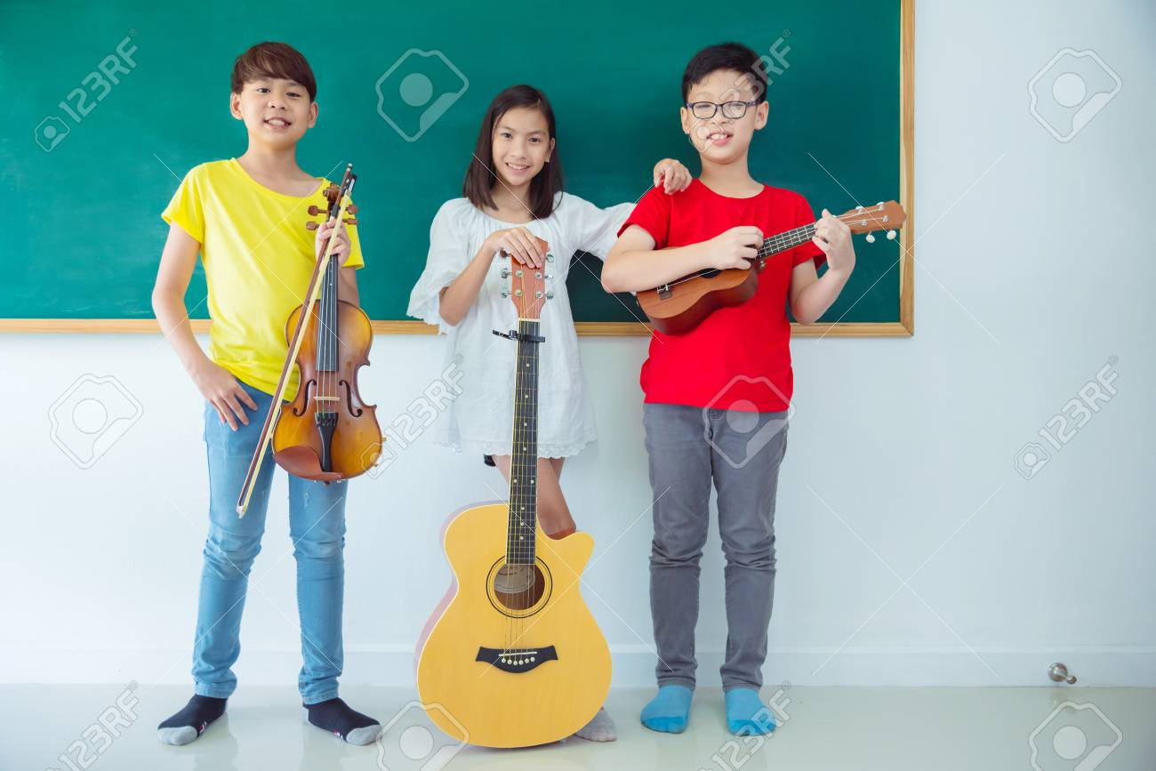 Group of happy Asian kids with Music Instruments standing and