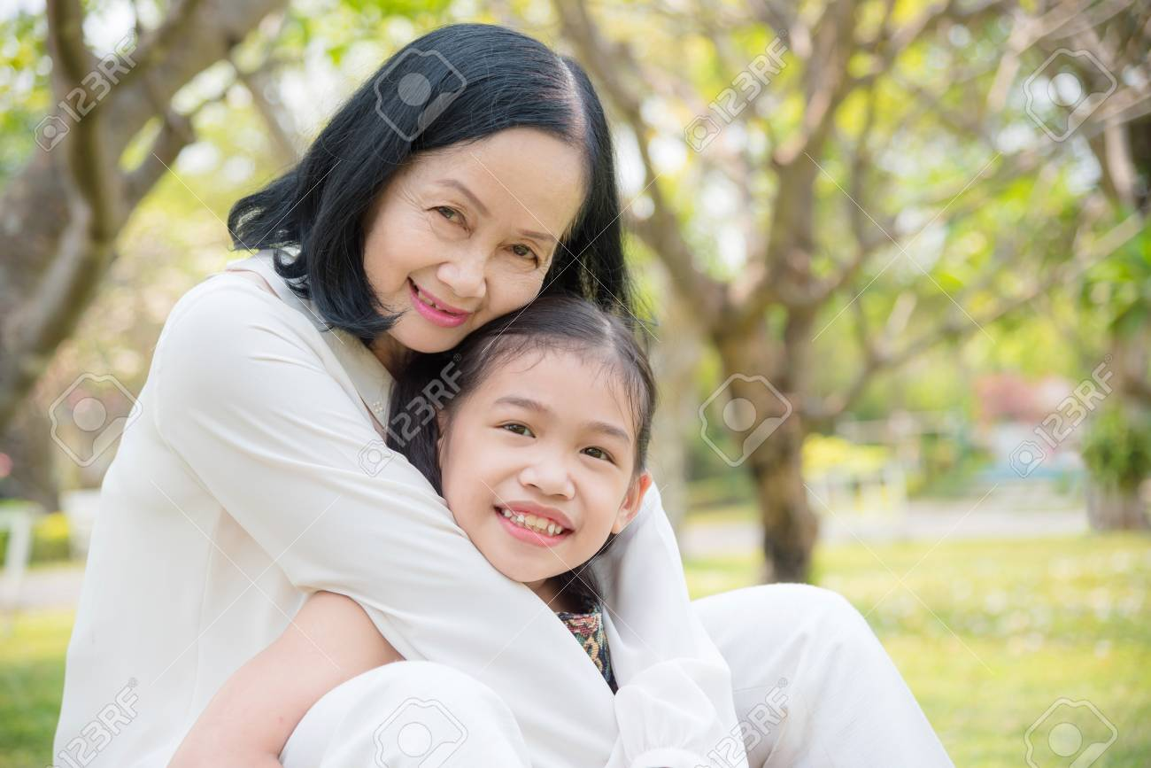 Asian Grandmother and granddaughter sitting together in the garden.Happy Asian family conception. - 121341902