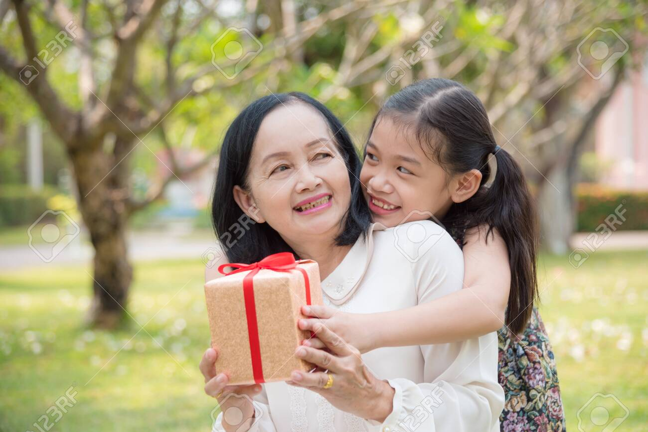 Asian granddaughter giving birthday gift for granddaughter in the garden.Happy Asian family conception. - 121342105