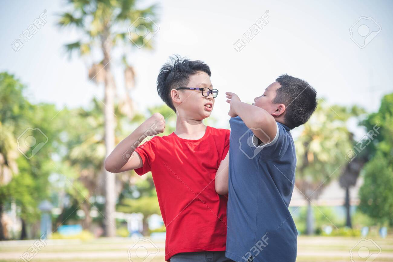 Asian schoolboy getting bullied ,Children fighting with classmate in school park. Bullying and violence in school concept. - 127896361