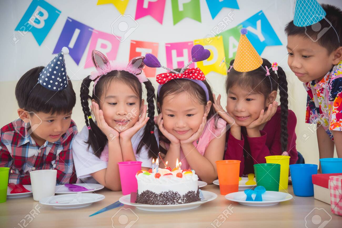 Marvelous Group Of Asian Kids Looking At Candle On Cake At Birthday Party Funny Birthday Cards Online Inifofree Goldxyz