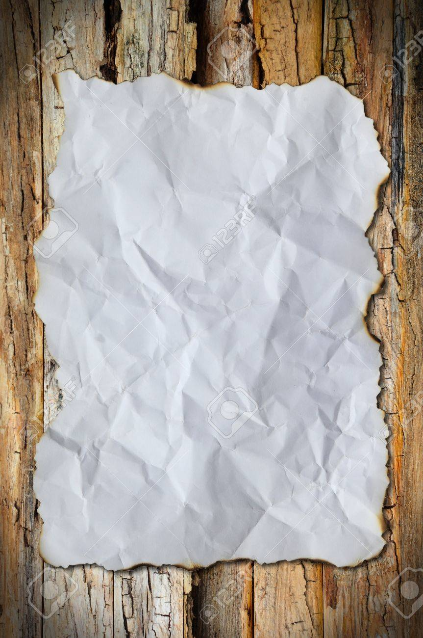white crumpled paper and border burn on wood background Stock Photo - 9631226