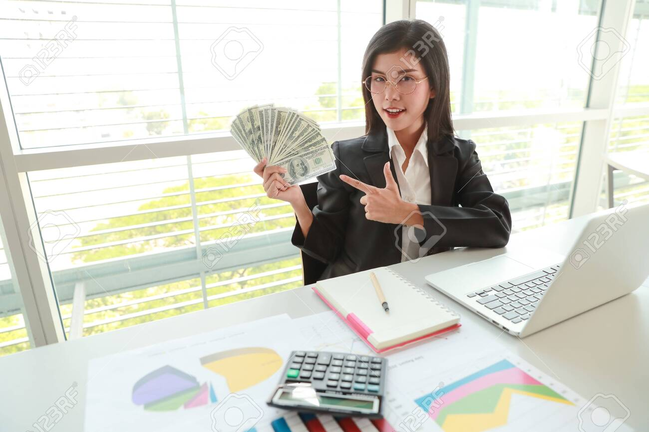 businesswoman showing company summary report and graph with money on hands - 130679575