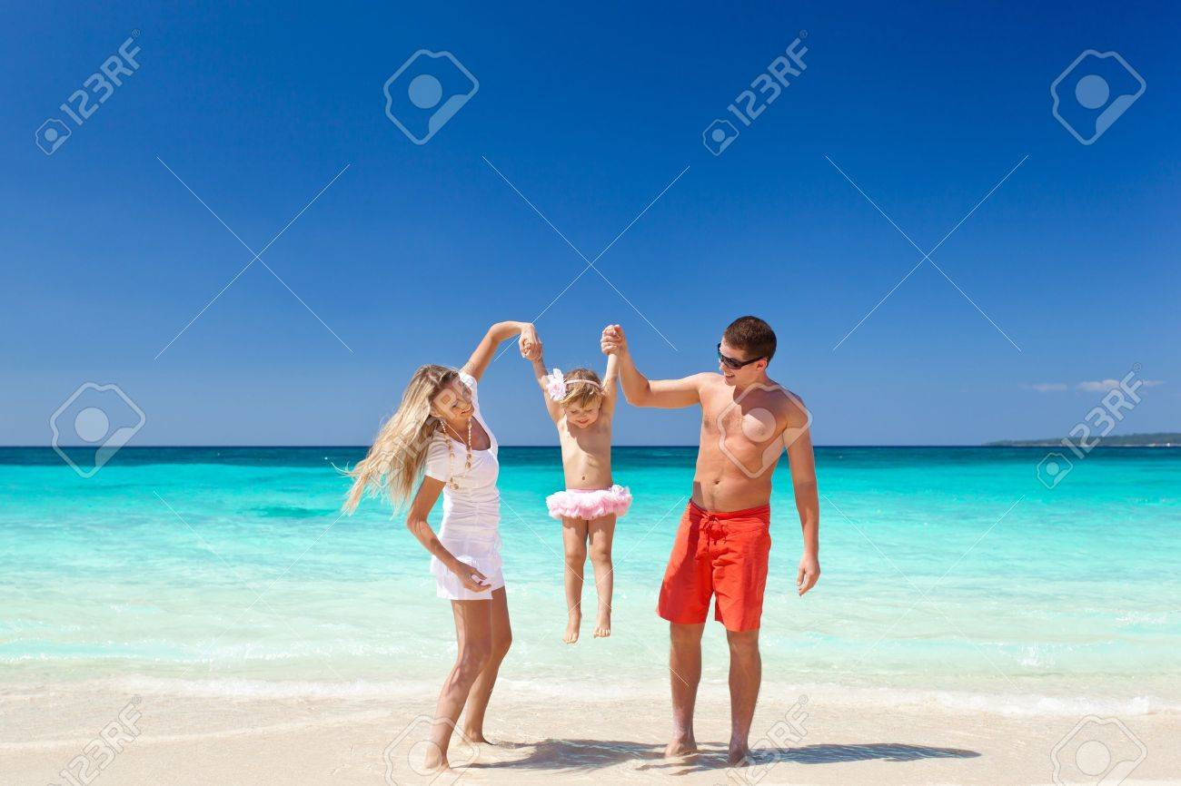 Parents throwing their daughter in air at the tropical beach Stock Photo - 19915647