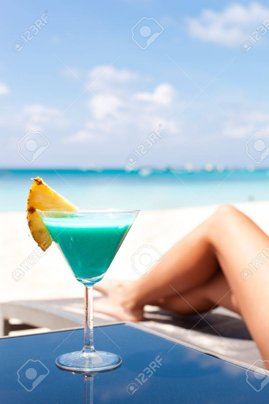 Resort Vacation. Woman relaxing with Blue Curacao Cocktail. (Focus is on glass) Stock Photo - 20335936